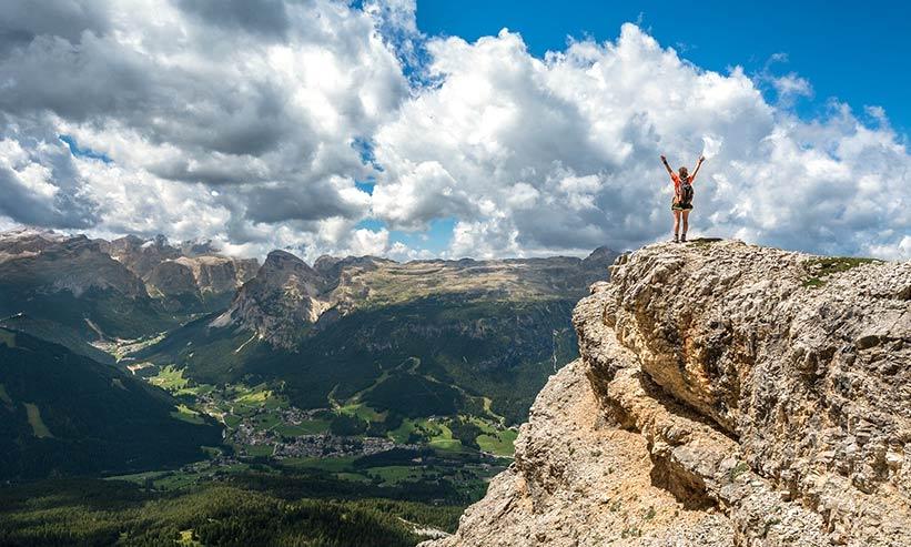 崖の上で両手を高くあげる女性