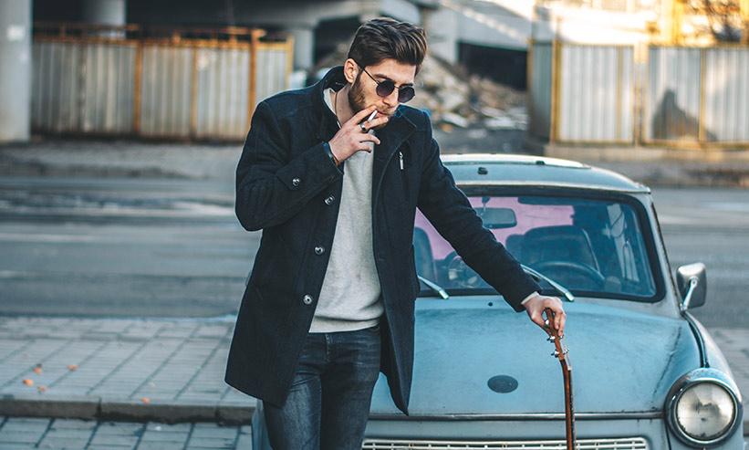 車の前でタバコを吸う男性