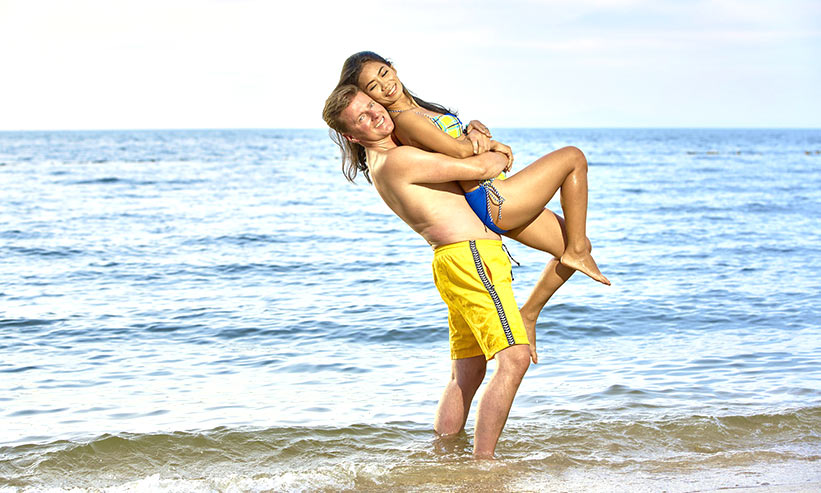 波打ち際ではしゃぐカップル