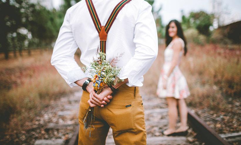 花束を隠し女性にプレゼントしようとする男性