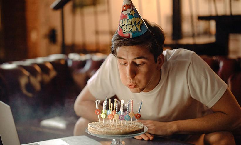 ケーキの蝋燭を消す男性