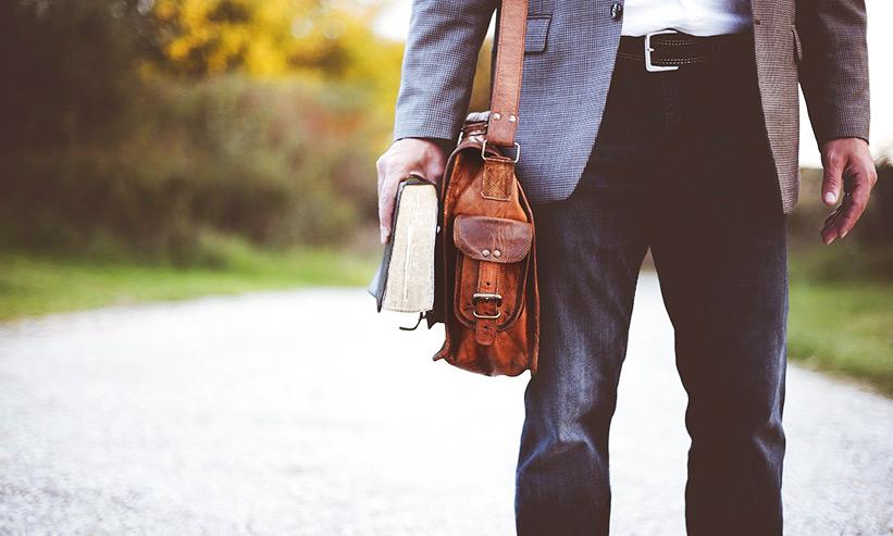 本とバッグを持っている男性