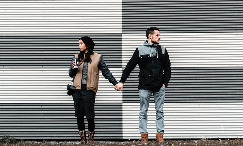 お互い違う方向を向いて手を繋ぐカップル