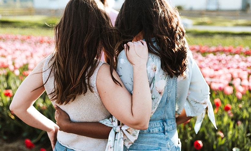 お互いの肩と腰に手を回す2人の女性