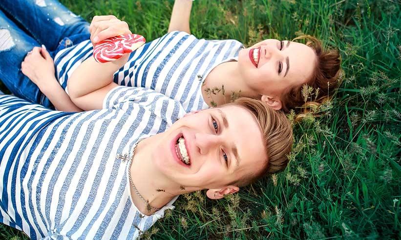 笑顔で草原に寝転ぶカップル