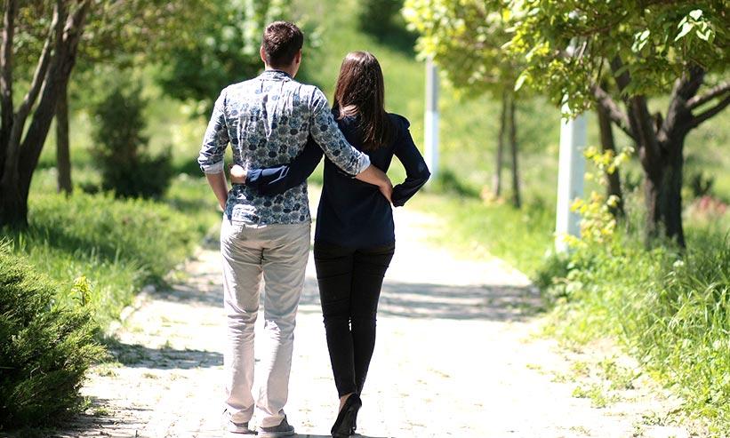 お互いの腰に腕を回し歩くカップル