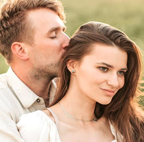 女性の後頭部にキスをする男性
