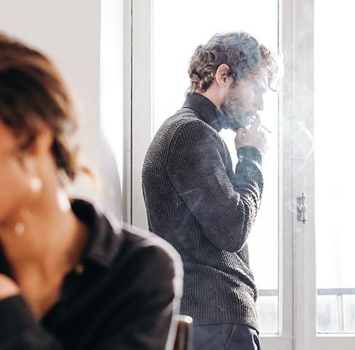窓際でタバコを吸う男性