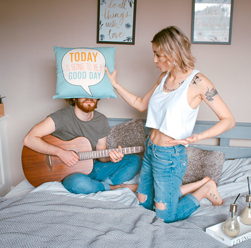 ギターを引いている男性の顔をクッションで隠す女性