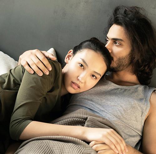 ベッドで横になるカップル