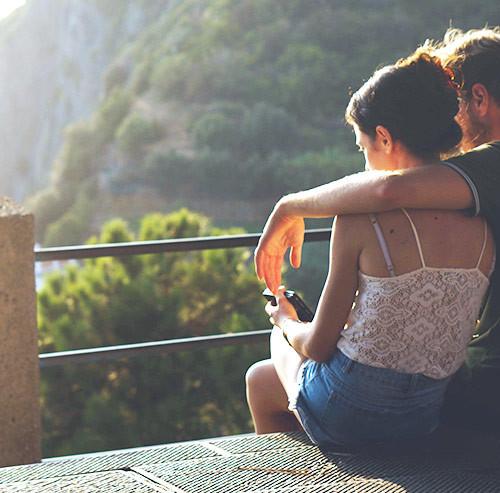 女性の肩に腕を回して座る男性