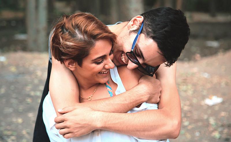笑いながら女性を抱きしめる男性