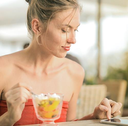 パフェを食べながらスマートフォンを操作する女性