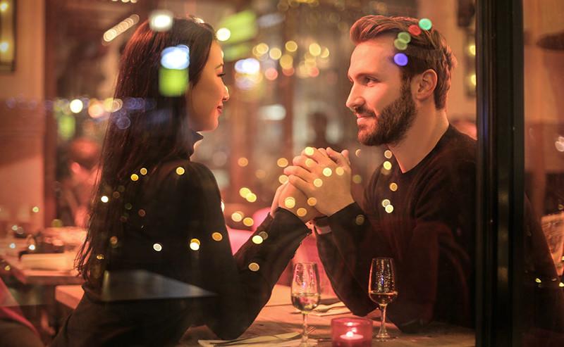 カフェで手を取り合い見つめ合うカップル