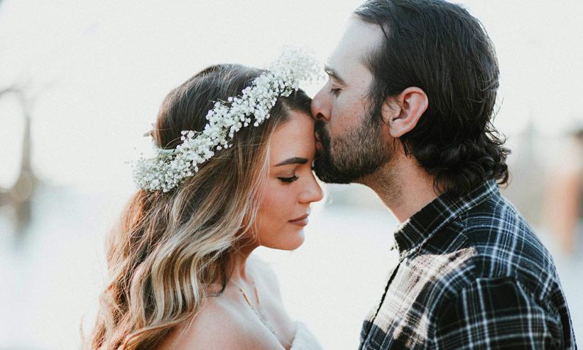 女性の額にキスをしている男性