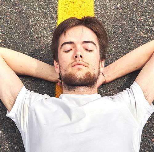 道端で寝転ぶ男性