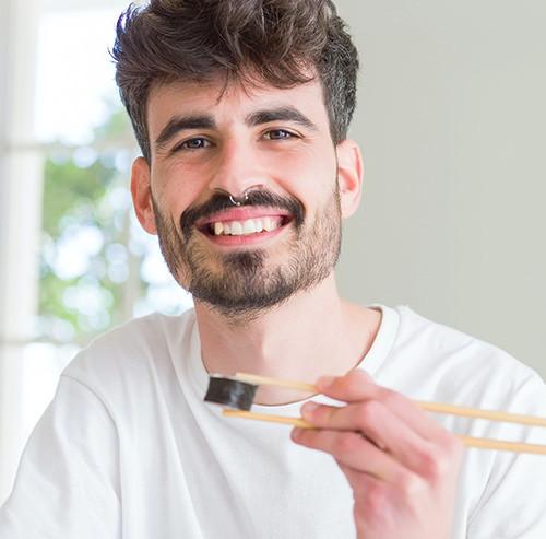 箸で巻き寿司を掴む男性