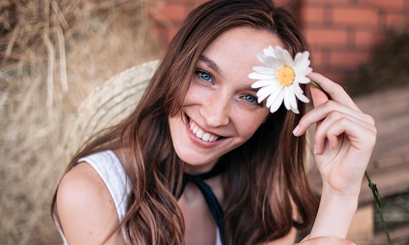 一輪の花を持ちニッコリ笑う女性