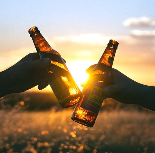 夕焼けの中ビールで乾杯する様子