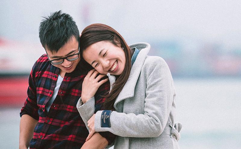 男性の肩に顔を近づけて笑う女性