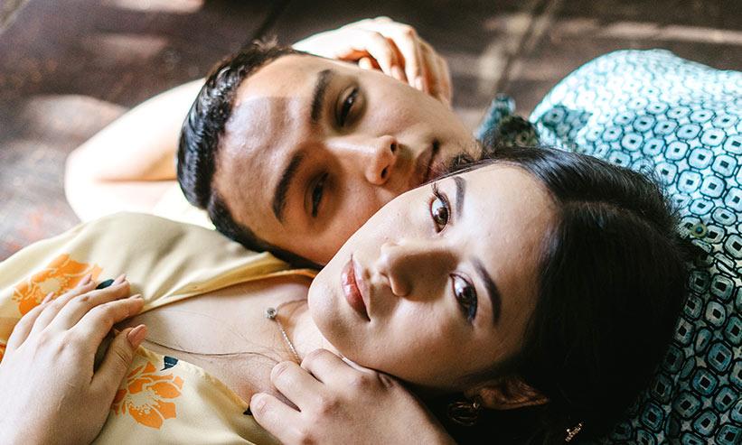 寝転びお互いの顔を近づけるカップル