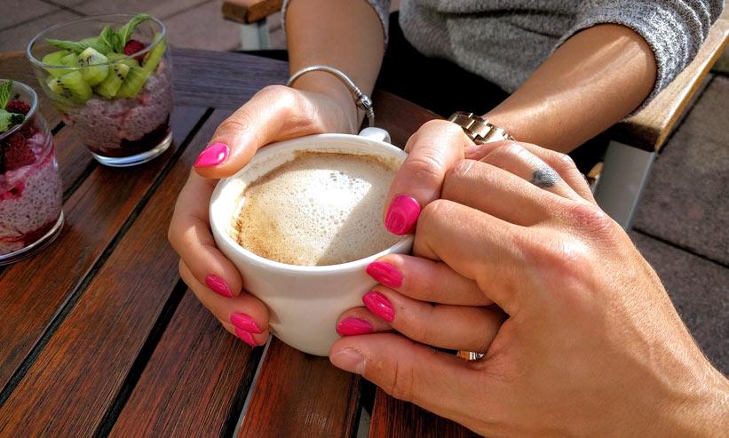コーヒーカップを持つ女性の手を握る男性
