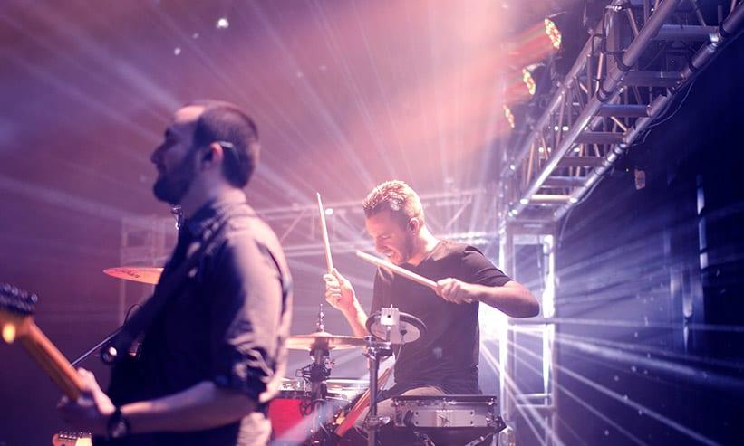 ライブでドラムを叩く男性とギターを弾く男性