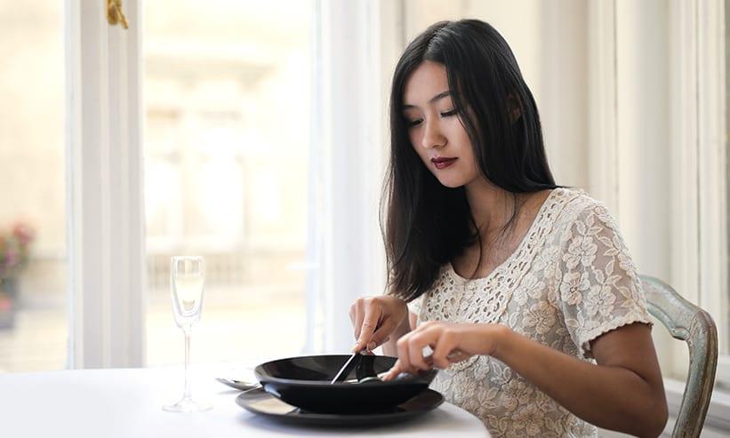 ナイフとフォークで食事をする女性