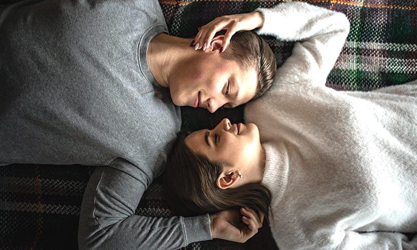 見つめあいながら寝転ぶカップル