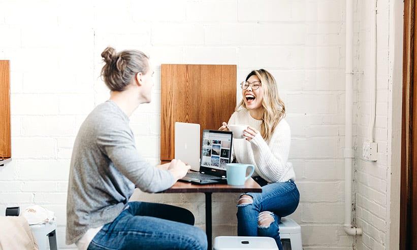カフェで笑いながら話すカップル