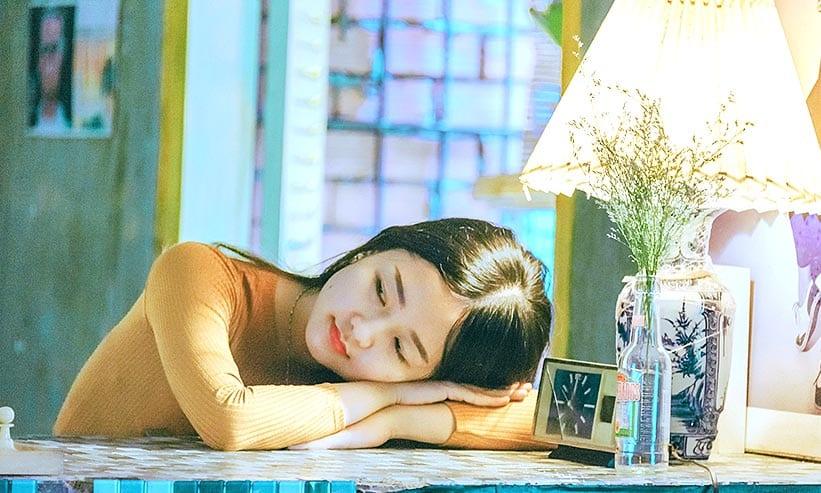 テーブルに頭を置き横を見ている女性