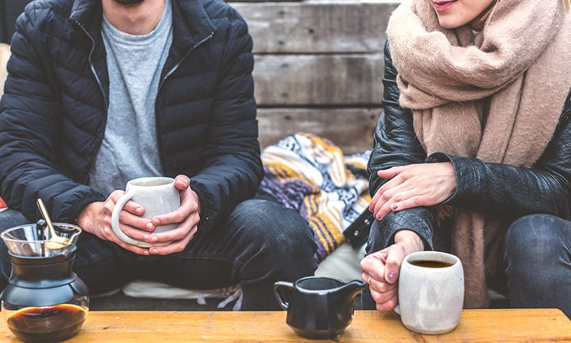 椅子に座ってコーヒーを飲む男女