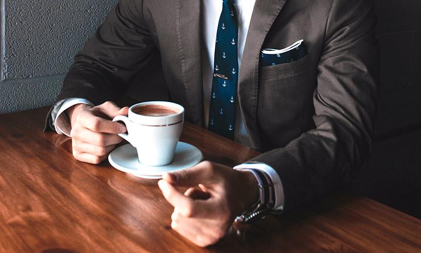 コーヒーを持つスーツの男性