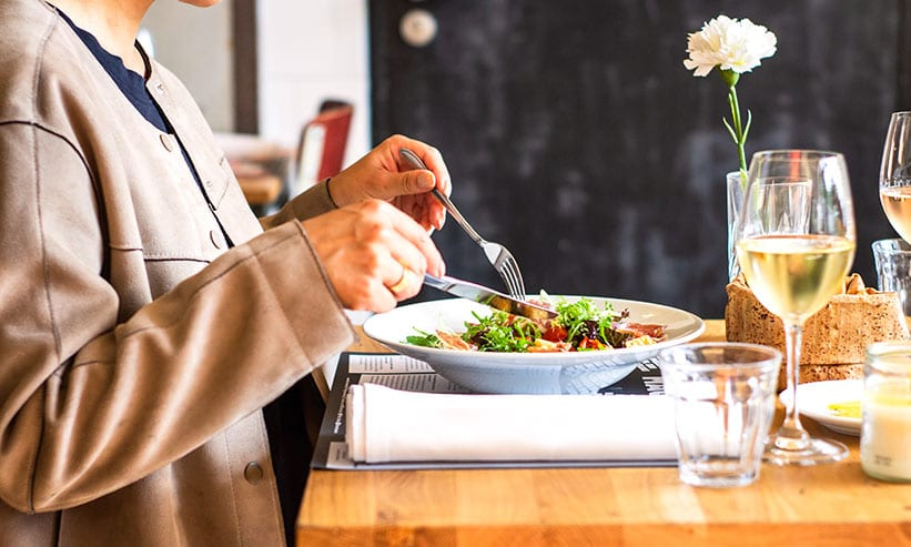 フォークとナイフで食事中の女性