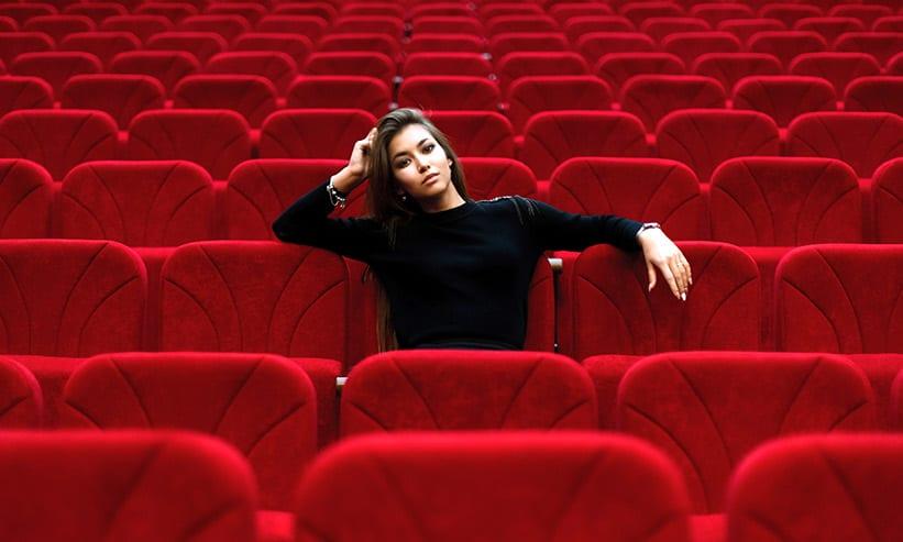 肘をつきながら映画を見る女性