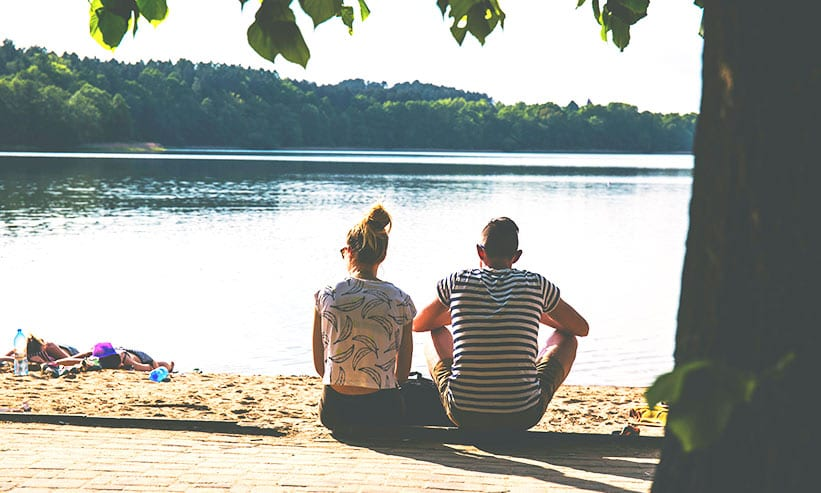 木陰に座り湖を眺めるカップル