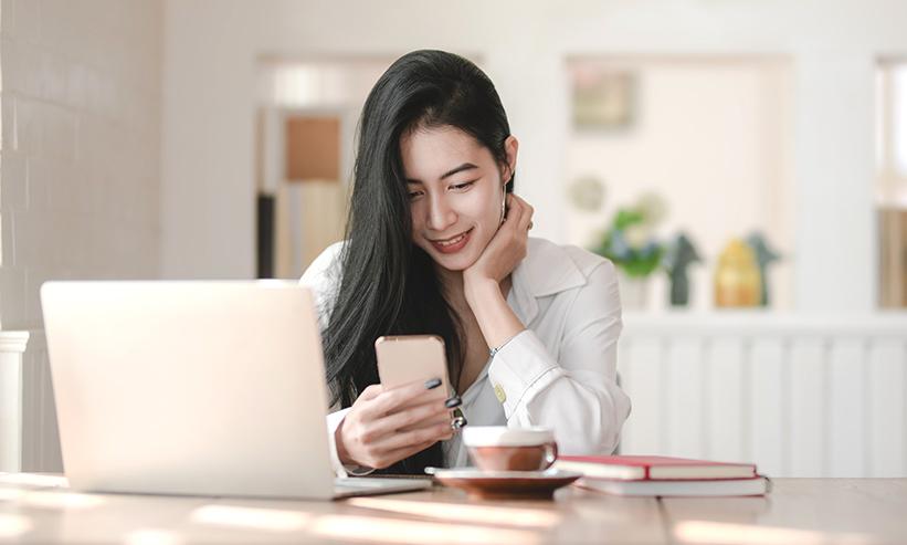 テーブルに座りスマートフォンを操作する女性