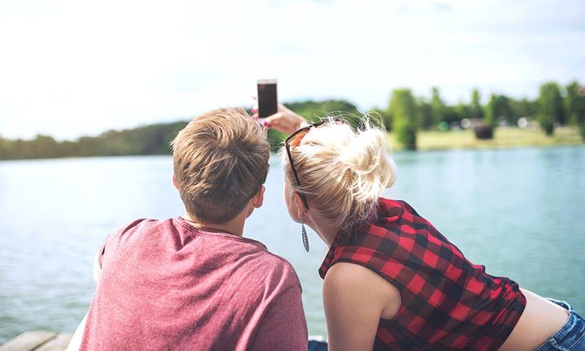 湖の前で自撮りしているカップル