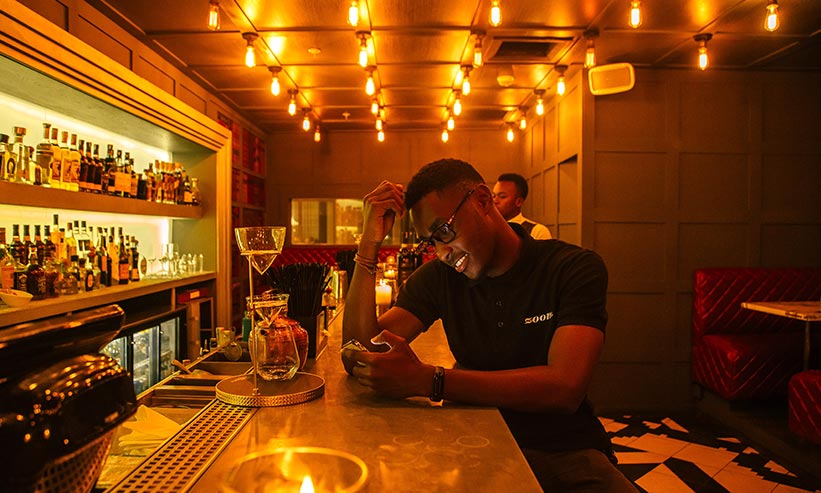バーでスマートフォンを見ている男性