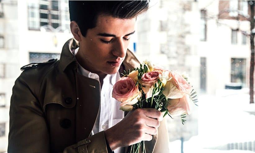 花の匂いを嗅ぐ男性