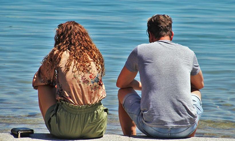湖を見ながら座っているカップルの後ろ姿