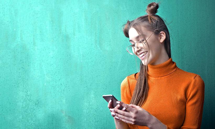 笑いながらスマートフォンを操作する女性