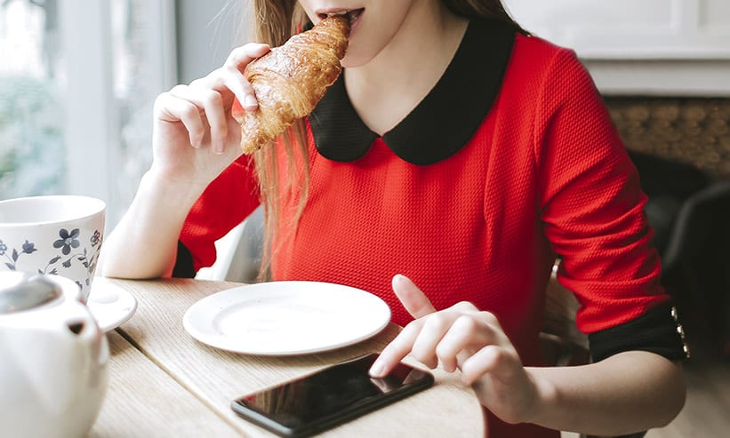 カフェでスマホを見ながらパンを食べる女性