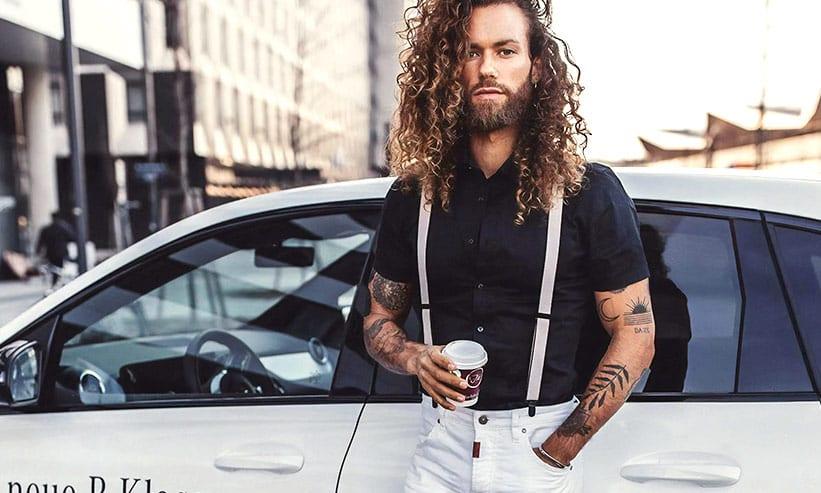車にもたれながらコーヒーを飲む男性