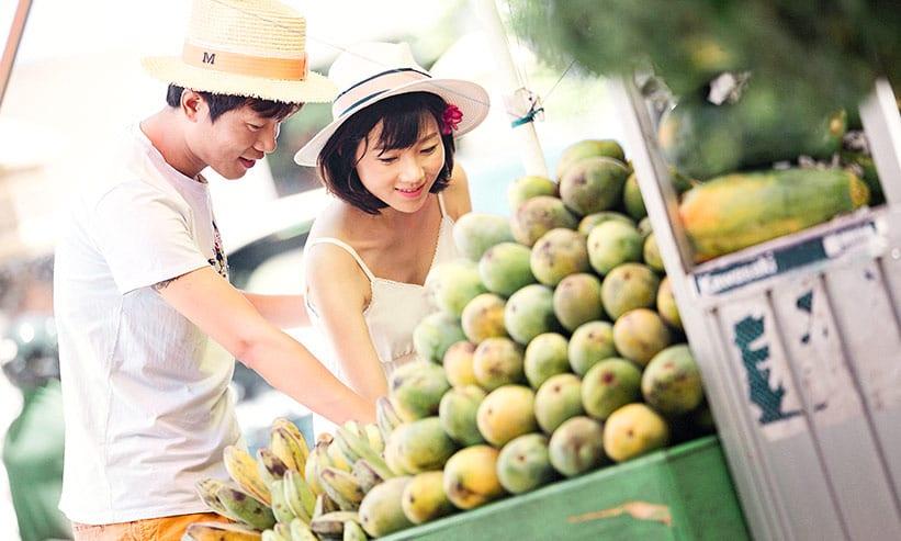 市場でフルーツを手に取ろうとしているカップル