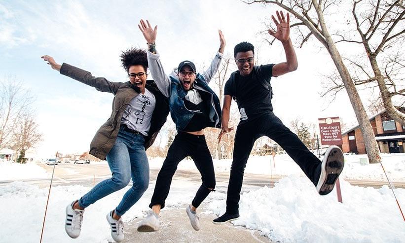 外でジャンプする3人の男女