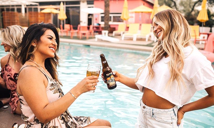 プールで乾杯する2人の女性