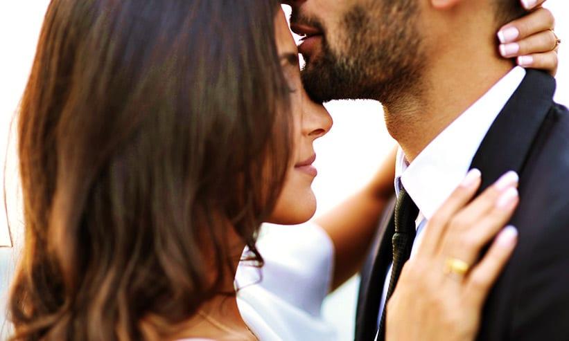 女性の額にキスをする男性