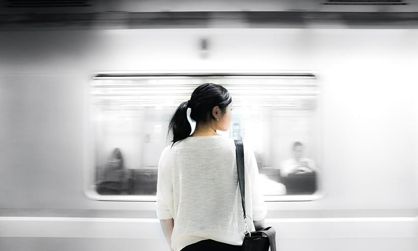 電車が通り過ぎるのを見ている女性