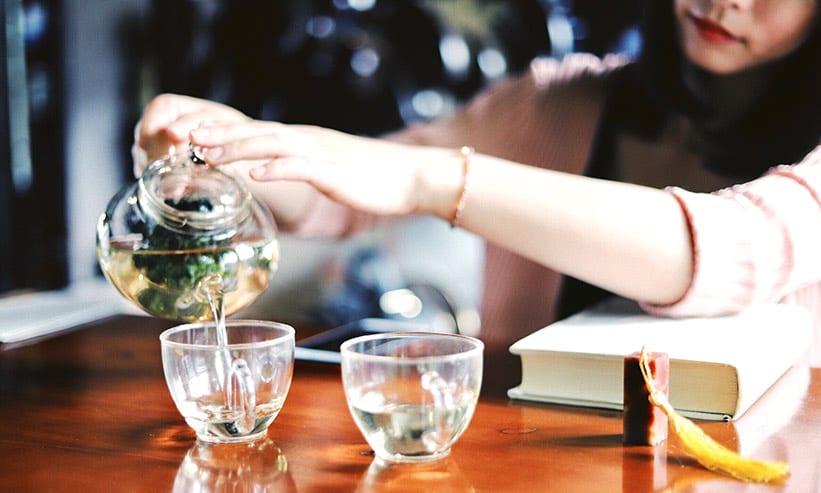 ハーブティーをグラスに注ぐ女性